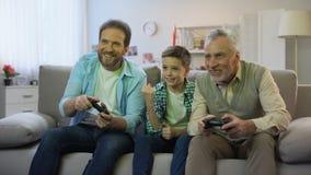 Αγόρι Preteen ενθαρρυντικό για τον μπαμπά και granddad το παίζοντας τηλεοπτικό παιχνίδι, pappy χρόνος, χόμπι απόθεμα βίντεο