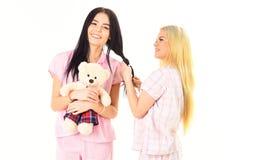 Αδελφές, καλύτεροι φίλοι στις πυτζάμες που κάνουν την πλεξούδα, hairdo μεταξύ τους Κορίτσια στις ρόδινες πυτζάμες, απομονωμένο άσ Στοκ Φωτογραφία