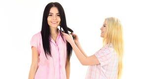 Αδελφές, καλύτεροι φίλοι στις πυτζάμες που κάνουν την πλεξούδα, hairdo μεταξύ τους Ξανθός, brunette στα πρόσωπα χαμόγελου στα ενδ Στοκ Φωτογραφία