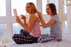 Αδελφές που απολαμβάνουν on-line και hairstyles ο ένας για τον άλλον στοκ εικόνες με δικαίωμα ελεύθερης χρήσης