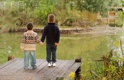 Αδελφοί που κοιτάζουν έξω πέρα από μια λίμνη το φθινόπωρο Στοκ εικόνες με δικαίωμα ελεύθερης χρήσης