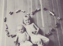 Αδελφοί που περικυκλώνονται από μια καρδιά που γίνεται από τα ξύλινα τραίνα και τα οχήματα στοκ φωτογραφίες