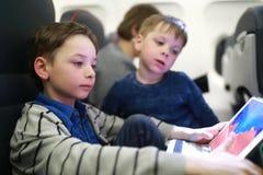 Αδελφοί που χρησιμοποιούν την ταμπλέτα στο αεροπλάνο στοκ φωτογραφία