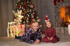 Αδελφός και αδελφή κοντά στο χριστουγεννιάτικο δέντρο στοκ εικόνα