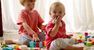 Αδελφός και αδελφή που παίζουν τους πλαστικούς φραγμούς απόθεμα βίντεο