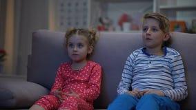 Αδελφός που αγκαλιάζει τη φοβησμένη αδελφή προσέχοντας τη νύχτα ταινιών φρίκης μαζί, οικογένεια απόθεμα βίντεο
