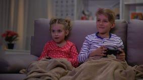 Αδελφός που αστειεύεται με την αδελφή που καλύπτει με το κάλυμμα, παιδιά που παίζει τη νύχτα παιχνίδι online απόθεμα βίντεο