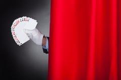 Αερισμένες εκμετάλλευση κάρτες μάγων πίσω από τη σκηνική κουρτίνα Στοκ Φωτογραφία