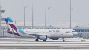 Αεριωθούμενα αεροπλάνα κονδόρων και Eurowings που κάνουν το ταξί στον αερολιμένα του Μόναχου, χιόνι φιλμ μικρού μήκους