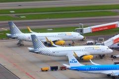 Αεριωθούμενα αεροπλάνα Vueling που σταθμεύουν στην πύλη Schiphol Στοκ Φωτογραφία