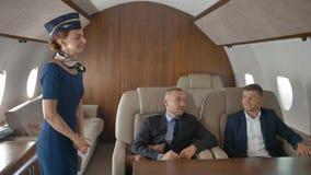 Αεριωθούμενο αεροπλάνο επιχειρηματιών ιδιωτικά που χαλαρώνει πετώντας και μιλώντας με την αεροσυνοδό φιλμ μικρού μήκους