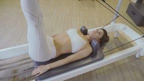 Αεροβική γυναίκα εκπαιδευτικών Pilates στην άσκηση ικανότητας μεταρρυθμιστών κάνετε τις διασπάσεις απόθεμα βίντεο