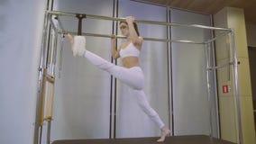 Αεροβική γυναίκα εκπαιδευτικών Pilates στην άσκηση ικανότητας cadillac κάνετε τις διασπάσεις απόθεμα βίντεο