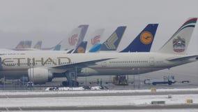 Αεροπλάνα στις τελικές πύλες στον αερολιμένα του Μόναχου, χειμώνας με το χιόνι απόθεμα βίντεο