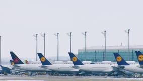 Αεροπλάνα της Lufthansa στις τελικές πύλες, αερολιμένας του Μόναχου, χειμώνας με το χιόνι απόθεμα βίντεο