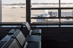 Αεροπλάνο, άποψη από το τερματικό αερολιμένων με τις άδειες θέσεις στη αίθουσα αναμονής αερολιμένων κοντά στην πύλη μικρό ταξίδι  Στοκ φωτογραφία με δικαίωμα ελεύθερης χρήσης