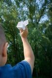 Αεροπλάνο εγγράφου στα χέρια παιδιών στο υπόβαθρο πρασινάδων και μπλε ουρανός στην ηλιόλουστη θερινή ημέρα Έννοια του καλοκαιριού στοκ φωτογραφίες