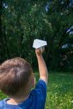 Αεροπλάνο εγγράφου στα χέρια παιδιών στο υπόβαθρο πρασινάδων και μπλε ουρανός στην ηλιόλουστη θερινή ημέρα Έννοια του καλοκαιριού στοκ εικόνες