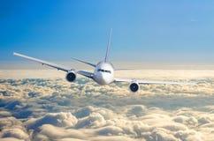 Αεροπλάνο επιβατών που πετά σε επίπεδο πτήσης υψηλό στον ουρανό επάνω από την ανατολή σύννεφων και μπλε ουρανού Στοκ Εικόνες