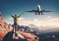 Αεροπλάνο και άτομο στην πέτρα με αυξημένος επάνω στα όπλα στοκ φωτογραφίες με δικαίωμα ελεύθερης χρήσης