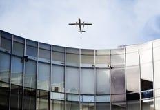 Αεροπλάνο πέρα από το κυρτό κτήριο Στοκ Φωτογραφία