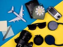 Αεροπλάνο παιχνιδιών, κάμερα, γυαλιά ηλίου, ακουστικά, πορτοφόλι, κάμερα δράσης και σακίδιο πλάτης στοκ εικόνες