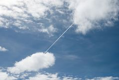 Αεροπλάνο που διασχίζει τον ουρανό από το σύννεφο στο σύννεφο στοκ εικόνες