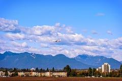 Αεροπλάνο που πετά κάτω από τα σύννεφα πέρα από τα κτήρια στοκ φωτογραφία με δικαίωμα ελεύθερης χρήσης