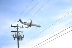 Αεροπλάνο στο μπλε ουρανό επάνω από τον ηλεκτρικούς πόλο και τα καλώδια στοκ φωτογραφία με δικαίωμα ελεύθερης χρήσης