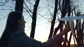 Αεροπλάνο τρεξίματος γυναικών και εγγράφου ενάρξεων στο κλίμα ηλιοβασιλέματος Έννοια της επιθυμίας να πάει στις διακοπές ή το ταξ απόθεμα βίντεο