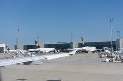 Αεροπλάνα της Lufthansa και σταθμευμένο εξοπλισμός εξωτερικό τερματικό ι αερολιμένων Στοκ εικόνες με δικαίωμα ελεύθερης χρήσης