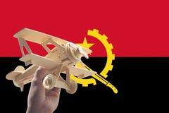 Αεροπλάνο αεροπλάνων εκμετάλλευσης χεριών πέρα από τη σημαία της Ανγκόλα, έννοια ταξιδιού Στοκ Φωτογραφίες