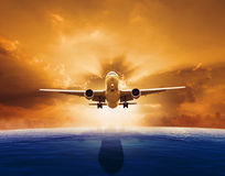 Αεροπλάνο επιβατικών αεροπλάνων που πετά πέρα από την όμορφη θάλασσα - επίπεδο με το σύνολο ήλιων Στοκ φωτογραφία με δικαίωμα ελεύθερης χρήσης
