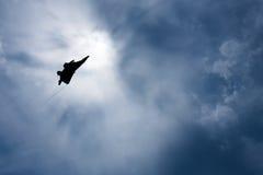 Αεροπλάνο μαχητών αναδρομικά φωτισμένο από τον ήλιο σε έναν σκοτεινό, νεφελώδη ουρανό Στοκ φωτογραφία με δικαίωμα ελεύθερης χρήσης