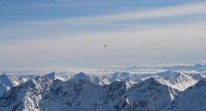 Αεροπλάνο πέρα από τα βουνά στοκ εικόνα με δικαίωμα ελεύθερης χρήσης