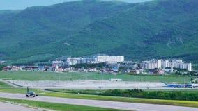 Αεροπλάνο που απογειώνεται από το αεροδρόμιο με το υπόβαθρο των βουνών και του β απόθεμα βίντεο