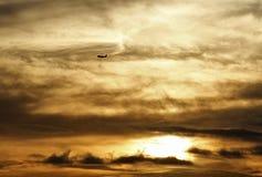 Αεροπλάνο που πετά πέρα από τα σύννεφα σε ένα χρυσό ηλιοβασίλεμα Στοκ Φωτογραφίες
