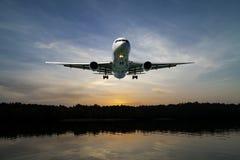 Αεροπλάνο που πετά στην τροπική θάλασσα ουρανού στο χρόνο ηλιοβασιλέματος Στοκ Φωτογραφίες