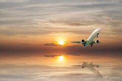 Αεροπλάνο που πετά την τροπική θάλασσα στο χρόνο ηλιοβασιλέματος με την αντανάκλαση Στοκ Εικόνα