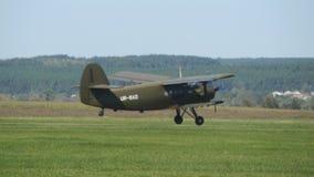 Αεροπλάνο που προσγειώνεται στον αερολιμένα Το παλαιό αεροπλάνο με τους γύρους προωστήρων πέρα από τον τομέα της πράσινης χλόης σ απόθεμα βίντεο
