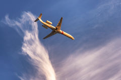 Αεροπλάνο στον ουρανό στο ηλιοβασίλεμα με τα φω'τα προσγείωσης επάνω Στοκ εικόνα με δικαίωμα ελεύθερης χρήσης