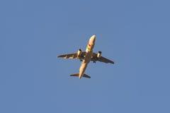 Αεροπλάνο στον ουρανό στο ηλιοβασίλεμα με τα φω'τα προσγείωσης επάνω Στοκ Εικόνες