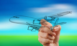 Αεροπλάνο σχεδίων χεριών στο μπλε ουρανό θαμπάδων στοκ εικόνες