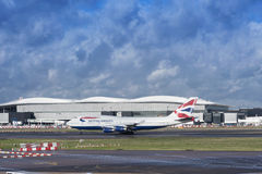 Αεροπλάνο της British Airways που απογειώνεται στον αερολιμένα Heathrow στο νεφελώδες δ Στοκ Εικόνες