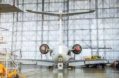 Αεροσκάφη επιβατών στη συντήρηση της επισκευής μηχανών και ατράκτων στο υπόστεγο αερολιμένων Οπισθοσκόπος της ουράς Στοκ Φωτογραφία