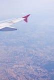 Αεροσκάφη φτερών σε ένα κλίμα του μπλε ουρανού και των σύννεφων Η όψη από την παραφωτίδα Στοκ Εικόνα