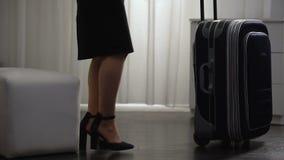 Αεροσυνοδός που αφήνει το δωμάτιο ξενοδοχείου για την πτήση, που φέρνει τις αποσκευές, επαγγελματικό ταξίδι απόθεμα βίντεο