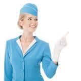 Αεροσυνοδός μπλε σε ομοιόμορφο δείχνοντας το δάχτυλο στοκ φωτογραφίες