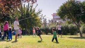 Αθήνα, Ελλάδα στις 4 Οκτωβρίου 2015 Παιδιά που παίζουν στα παλαιά παραδοσιακά παιχνίδια πάρκων στοκ εικόνα