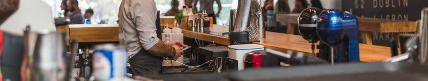 ΑΘΗΝΑ, ΕΛΛΑΔΑ - 17 ΣΕΠΤΕΜΒΡΊΟΥ 2018: Νέο όμορφο bartender που χρησιμοποιεί το smartphone μπροστά από το φραγμό στοκ φωτογραφίες